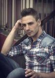 Attractaive młodego człowieka obsiadanie na zmielony plenerowym zdjęcie stock