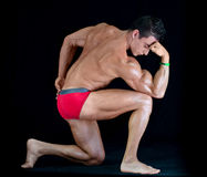 Attractiave young muscle man in classic pose on his knee Royalty Free Stock Images