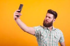 Attractice uppsökte mannen i skjortan som tar en selfie över gul bakgrund fotografering för bildbyråer