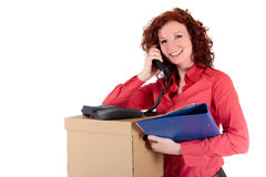 Attractice young businesswoman. Attractive young businesswoman  beside a stack of storage-boxes speaking on telephone and holding a folder. Studio shot. White Royalty Free Stock Photo