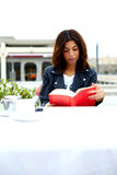 Attractie female hipster enjoying a good book in cafe during her recreation time at weekend Stock Image