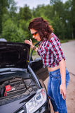 Attractie woman in front of broken car's engine Stock Image