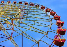 Attraction in an amusement park carousel Ferris wheel on a background of a blue sky during the day Stock Photography