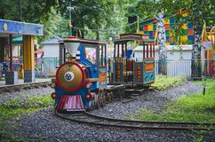 Kids railway in the park. Attraction in the amusement park. Kid`s railway with colorful locomotive and wagon stock photography