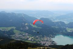 St. Gilgen, Austria: Red and yellow paragliders flying over the mountains royalty free stock photo