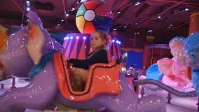 Attraction d'enfants Équitation de petite fille sur un manège d'éléphant d'enfant en parc de jeu au centre de mail banque de vidéos