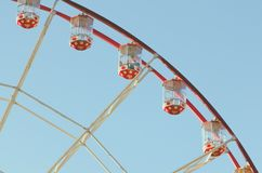 An attraction of a Ferris wheel against a blue sky background. The cabin of Ferris wheels closeup Stock Photo