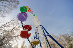 Attraction Ferris wheel with colored cabins in a winter park wit. H white snow Royalty Free Stock Image