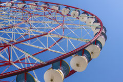 The attraction of a Ferris wheel with red and blue cabins in a children`s amusement park in the city on a blu. The attraction of a Ferris wheel with red and blue Stock Photography