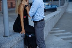 Happy loving couple hugging, date in the city. black dress, blue shirt and gray pants.attraction.the man picked up the woman`s. Attraction.happy loving couple royalty free stock photos