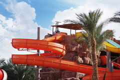 Attraction with a water pipe in the aqua park. Colorful water park tubes and a swimming pool Royalty Free Stock Images