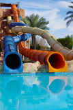 Attraction with a water pipe in the aqua park. Colorful water park tubes and a swimming pool Stock Images