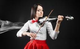 Attractiv ewoman som spelar fiolen på en svart bakgrund Royaltyfria Foton