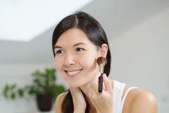 Attractiv happy woman applying makeup Royalty Free Stock Photography