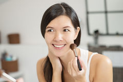 Attractiv happy woman applying makeup Royalty Free Stock Image