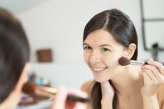 Attractiv happy woman applying makeup Stock Photos