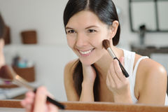 Attractiv happy woman applying makeup Stock Photography