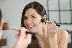Attractiv happy woman applying makeup Stock Photos
