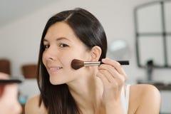 Attractiv happy woman applying makeup Royalty Free Stock Photos