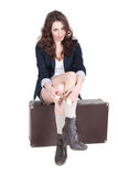 Attractiva girl is sitting on vintage suitcase Stock Photography