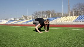 Attractive active fit young woman does yoga stretch pose on huge stadium green grass meditating calmly on warm sunny day stock video
