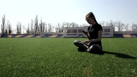 Attractive active young fit woman sitting on huge stadium green grass meditating calmly enjoying warm sunny spring day stock video