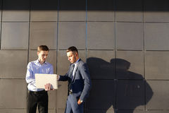 Attractive active young male man, businessman, student holds lap. Handsome confident young male man, businessman, student holds laptop in hands and deliver Royalty Free Stock Photography
