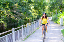 Attractive active young woman riding a bicycle. Along a road alongside a leafy shady canal approaching the camera with a smile stock photography