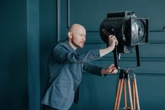 Attractive adult bald man with beard in suit looking at old lighting fixture, video light stock photography