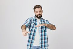 Attractive adult bearded husband in plaid shirt dancing hip hop showing yo gesture with hands, standing against gray. Wall. Dad tries convince teenage daughter Stock Photography