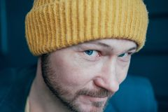 Attractive adult bearded man hipster in yellow hat looking into camera and smilingon blue wall background, close up stock images