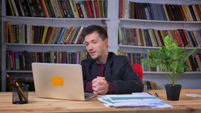 Attractive adult businessman having a video call on the laptop sitting in the office with bookshelves on the background stock video footage