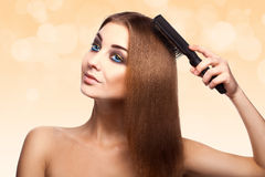 Attractive adult caucasian girl with blue eyes combing her perfe Royalty Free Stock Photos