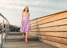 Attractive adult girl in pink dress and red shoes walking on woo Stock Image