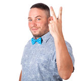 Attractive adult man with beard in a blue bow tie in summer shirt shows the gesture with hands on an isolated white background Royalty Free Stock Image