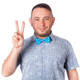 Attractive adult man with beard in a blue bow tie in summer shirt shows the gesture with hands on an isolated white background Royalty Free Stock Images