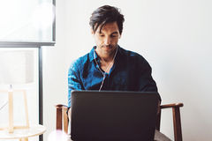 Attractive adult man making video conversation with friends.Man using contemporary notebook on headphones while sitting. In vintage chair.Blurred background Royalty Free Stock Photos