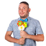 Attractive adult man with stubble in a bow tie in summer shirt holding a bouquet of flowers Royalty Free Stock Images