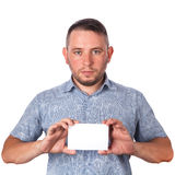 Attractive adult man with stubble in summer shirt in his hands holding a white sheet with space for advertising text on an isolate Royalty Free Stock Photo