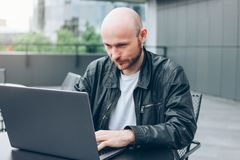 Attractive adult successful bald bearded man in black jacket with laptop in street cafe at city royalty free stock images