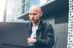Attractive adult successful bald bearded man in black jacket with laptop in street cafe at city stock photography