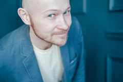 Attractive adult successful bald bearded man in suit looks into camera and smiles slyly on blue wall background royalty free stock photography