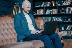 Attractive adult successful smiling bald man with beard in suit working at laptop on his rich cabinet royalty free stock photo