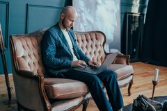 Attractive adult successful surprised bald man with beard in suit working at laptop on his rich cabinet. The Attractive adult successful surprised bald man with royalty free stock images