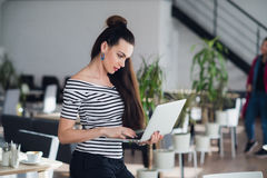 Attractive adult woman holding a laptop and typing a message to her subordinates to imform them about changes in. Schedule stock photography