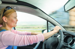 Attractive adult woman safe carefully driving car suburban road. Attractive adult woman safe and carefully driving car on suburban road. Inside the auto photo stock photo