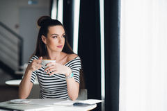 Attractive adult woman is sitting in a cafe and gazing through a window dreaming of someone, while holding a cup of hot. Coffee royalty free stock image