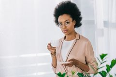 Attractive african american businesswoman drinking coffee. In office stock image