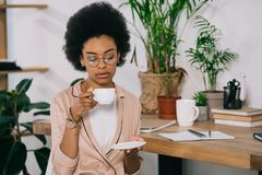 Attractive african american businesswoman drinking coffee in office during. Coffee break royalty free stock photo