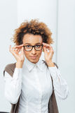 Attractive african american businesswoman in glasses standing in office Royalty Free Stock Image